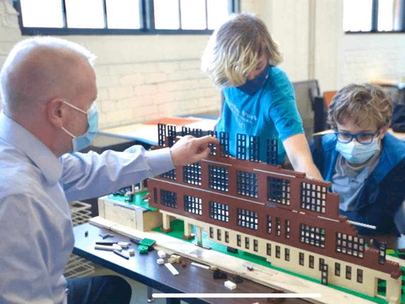 two menlo students with their teacher putting together a lego project